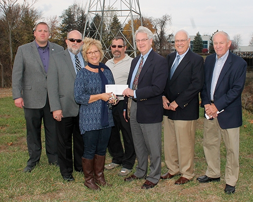 Members of The Heritage of Huntington Foundation present a check for $10,000 to the Huntington Area Recreation Trails Association (HARTA) at the future site of a picnic pavilion near the Erie Rail Bridge along Riverside Drive on Thursday, Nov. 5. Pictured (from left to right) are Anthony Goodnight, director of Public Works and Engineering Services for the City of Huntington; Huntington Mayor Brooks Fetters; Jody Schenkel-Davenport, HARTA president; Jim Lewis, HARTA; and Jim Flueckiger, Rev. James Jones and Phil Marshall, all of The Heritage of Huntington Foundation.