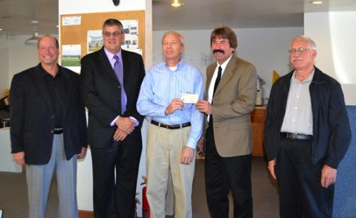 Kevin Cossairt (third from left), president of ALH Building Systems, in Markle, accepts a check for approximately $67,000 from Leon Hurlburt, president of the Huntington County Commissioners, to help pay for a fire protection system at his business.