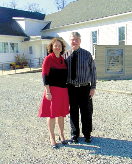Rev. Doug Sharrard (right), pastor of the Lancaster Wesleyan Church, and his wife Cheryl Sharrard stand in front of the church, which is celebrating its 125th anniversary with a hog roast and time of fellowship on Sunday, Oct. 28.