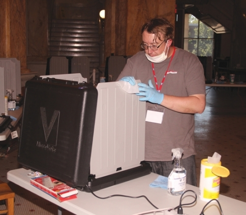 Tanner Runkle, a poll worker at the Huntington County Courthouse, cleans a voting machine after it was used by a voter on Election Day, Tuesday, June 2. Outfitted in masks and gloves, poll workers sanitized voting machines after every use to eliminate the possible presence of the COVID-19 virus.
