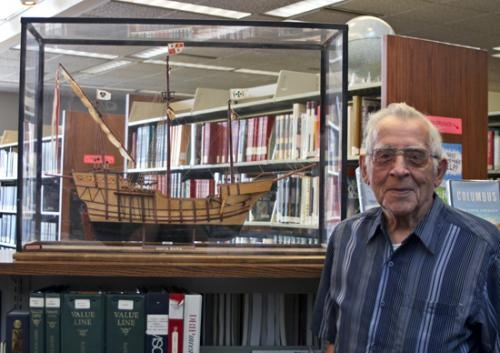 Model boat builder Bob Cline of Huntington stands with his reproduction of the Santa Maria, one of Christopher Columbus' ships, which is currently on display in the reference department of the Huntington City-Township Public Library.