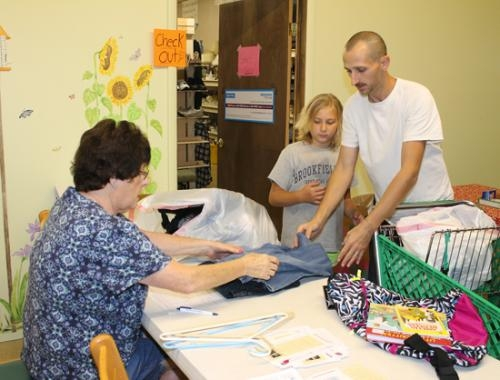 Ken Hostetler (right) and his daughter Savannah (center) check out with Roxanna Shumate at Love INC's clothing store, Covered With Love, in Huntington, on Thursday, Aug. 1.