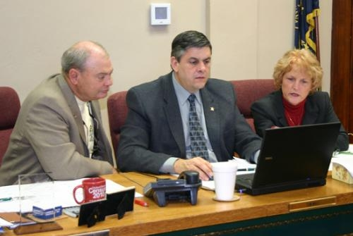 Huntington County Commissioners (from left) Jerry Helvie, Tom Wall and Kathy Branham do some work on Wall's laptop during the commissioners' meeting Monday, Jan. 4. The commissioners re-elected Wall as president and Branham as vice president.