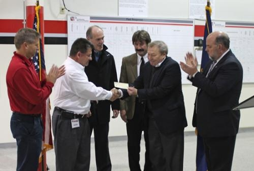 Mark Wickersham (second from left), executive director of Huntington County Economic Development, presents a grant for $50,000 to Frank Macher (fifth from left), chief executive officer of Continental Structural Plastics, on Wednesday, Nov. 14.