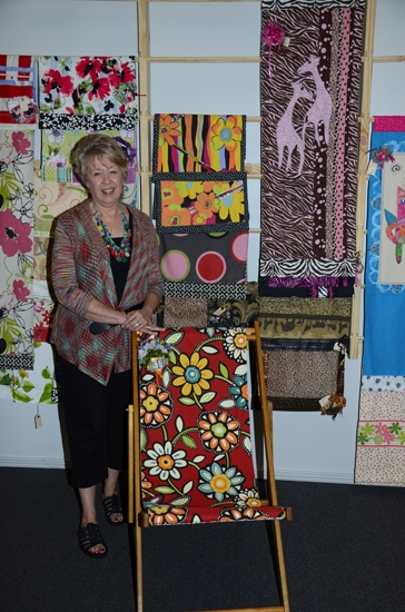 Ruth Swanson stands by a selection of merchandise for sale at her store, Courtyard Studio & Boutique, which recently re-opened in its new location at 123 N. Wayne St. in Warren.