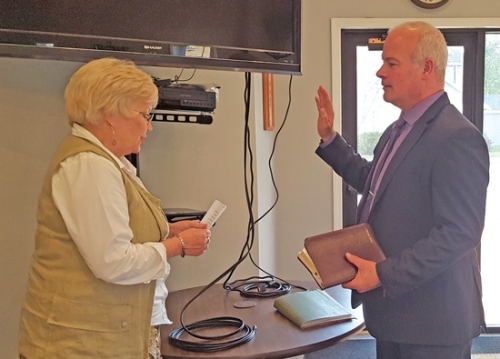 Holding a Bible, new Markle Town Councilman Matthew Doss is sworn into office by the town's clerk-treasurer, Carolyn Lane-Hamilton. The ceremony was held at the start of the regular town council meeting on Wednesday, May 15.
