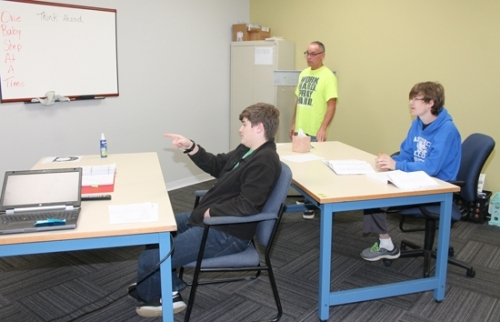 High school students Austin Kline (left) and Job Savage discuss a math concept presented during a video demonstration, as parent/teacher Tim McGuin (center) observes during class time Wednesday, Dec. 6, at Promise Education Cooperative. The homeschooling cooperative began in August in downtown Huntington.