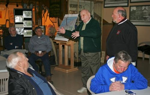 Retired Erie Railroader Martin Young (center) tells a story of what it was like to work on the railroad back in the day, as Huntington Mayor Brooks Fetters (standing at right) listens on Saturday, March 1.