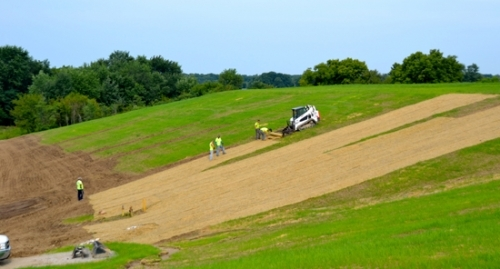 Landfill crews lay down cover for grass planted to help remedy erosion at several areas at the Huntington City Landfill.