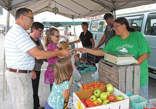 Bob Caley (left) purchases produce from Jackie Hobbs at the Downtown Farmers Market on the corner of Market and Warren streets, in Huntington, on Wednesday, July 31. The market is open every Wednesday from 4 p.m. to 7 p.m.