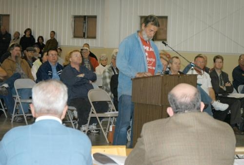 Huntington Common Council members Erv Ebersole and Brooks Fetters (from left, backs to camera) listen as Huntington resident Mark Krumanaker discusses a proposed trash fee during a packed public hearing Monday, Nov. 23, at Heritage Hall.