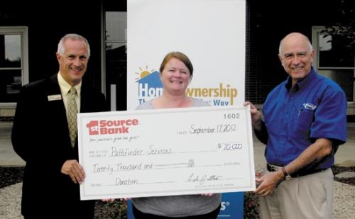 Lyle Juillerat (left), assistant vice president of 1st Source Bank in Huntington, presents a grant for $20,000 to John Niederman, president of Pathfinder Services, and Natalie Fisher, Home Buyer Education coordinator for Pathfinder Community on Sept. 17.