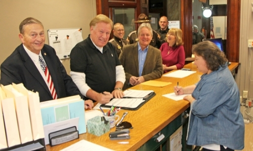 Candidates line up in the Huntington County Clerk's Office on the first day of candidate filing, Wednesday, Jan. 10, for the May 2018 primary. Pictured are (at desk, from left) Don Schoeff, running for auditor; Jay Poe, running for surveyor; Rob Miller, running for commissioner in the First District; and Vicki Pearson, running for recorder. Standing behind them are (from left) Chris Newton, who declared his candidacy for sheriff; current Huntington County Sheriff, Terry Stoffel; and Huntington County Sheriff's Department Deputy Chad Hammel. Assisting the candidates (at right) is Voter Registration and Election Deputy Pam Fowler.