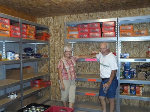 Sharon and Jerry Lockhart, volunteers at The Salvation Army food pantry, stand in front of the pantry's empty shelves.