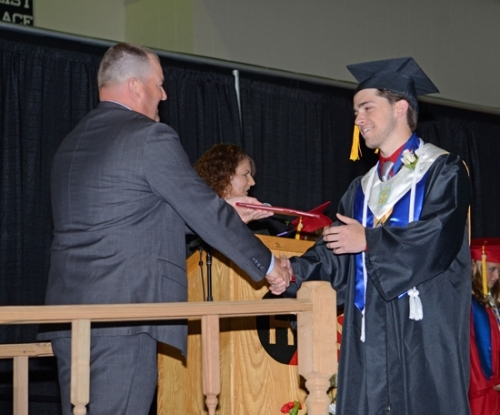 Huntington County Community School Corp. Board of School Trustees member Brian Warpup has a handshake and a diploma for Jacob Fowler at the 2018 Huntington North High School graduation ceremony on Sunday afternoon, June 3.