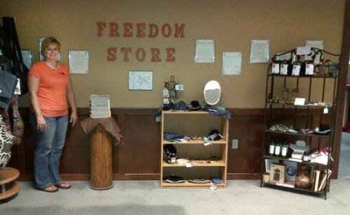 Melissa Gordon displays some of the items available at Freedom Store, now open at the Café of Hope.