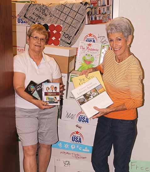 Sue Jepson (left) and Barb Hancher, president and publicity chair, respectively, for the Huntington Friends of the Library, pose with media that will be available for purchase at the group's Used Book Sale, which will be held at the Huntington Branch of the Huntington City-Township Public Library from Thursday, June 14, to Saturday, June 16.