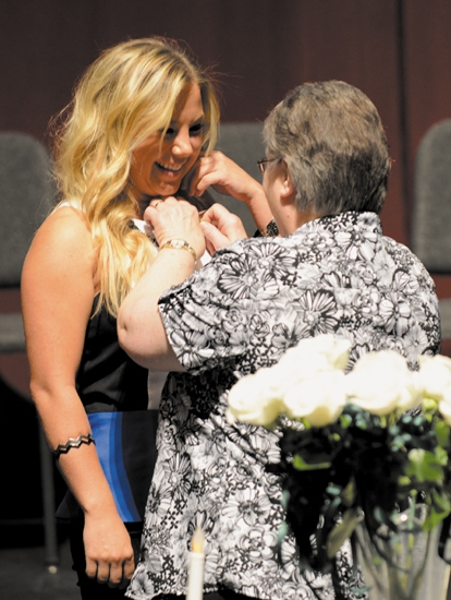 Brandi Gower (left) receives her nurse's pin from Dr. Margaret Winter, director of nursing at Huntington University's department of nursing, during a traditional pinning ceremony held on May 17 at HU for the 2013 nursing program graduates.
