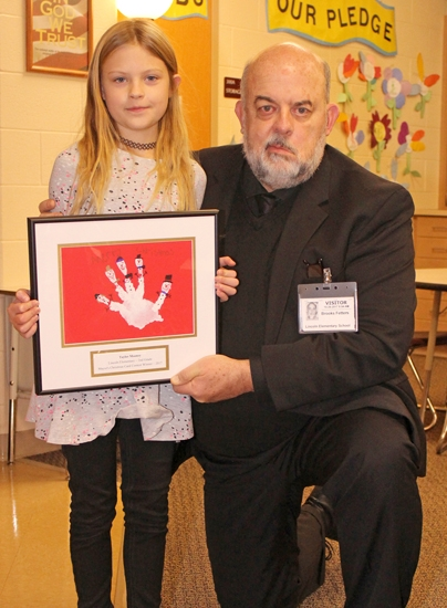 Mayor Brooks Fetters poses with second-grader Taylor Mooney on Thursday, Dec. 7, at Lincoln Elementary School upon announcing that her artwork was selected by the LaFontaine Arts Council as the winning entry in his annual Christmas card art contest. Mooney's art serves as the cover for the 2017 City of Huntington Christmas card.