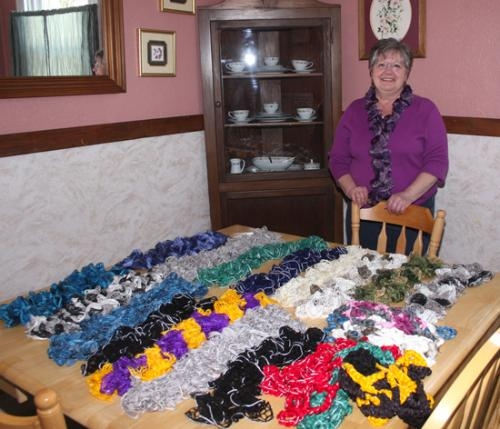 Carolyn Ray, Huntington House Shelter Supervisor, dons a ruffle scarf as she displays a table full of the variety of scarves available as part of the shelter's fund-raiser to help make updates to the home.