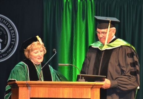 Dr. Sherilyn Emberton (left), president of Huntington University, presents an honorary doctorate of humane letters to lifelong Huntington resident Steve Platt during the school's 119th commencement ceremony Saturday afternoon, May 13, in the Merillat Complex Fieldhouse.