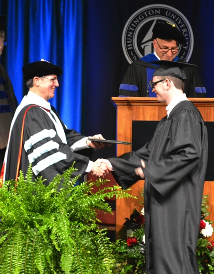 Huntington University President G. Blair Dowden (left) presents a diploma to Brett Evans during the school's commencement ceremony on Saturday, May 18, in the HU fieldhouse. Evans, of Huntington, earned a Bachelor of Arts in history.