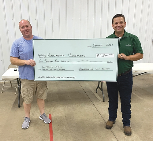 Matt Buckland (left), president of the Huntington County Swine Boosters, presents a $2,500 check to Nate Perry, managing director for the Haupert Institute for Agricultrual Studies. The gifted money will be used toward the Don Strauss Animal Science Education Center at Huntington University.