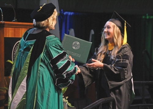 Tenessa Merryman (right) accepts her Doctorate of Occupational Therapy diploma from Dr. Sherilyn Emberton, president of Huntington University, during the school's 121st commencement ceremony on Saturday, May 18, in the Merillat Complex Fieldhouse. Merryman was one of 289 students in the school's 2019 graduating class.
