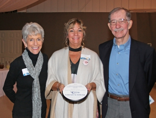 Pathfinder Services activities specialist Sarah Schwab (center) holds the 2017 Timothy Hancher Direct Support Service Award, presented at Pathfinder's annual dinner Thursday, Nov. 9, by Barbara (left) and Bill Hancher. Schwab has worked at the organization since 2009. The award, presented each year to an exceptional employee, includes a check for $250.