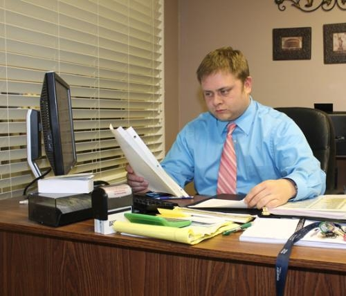 Brandon Kastner, the new administrator at Hickory Creek at Huntington, works in his office on Friday, Feb. 8.