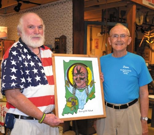Gary Davisson (left), winner of the adult division of the Huntington County Historical Society's art show, displays his winning work with the help of David Heiney (right), a museum volunteer.