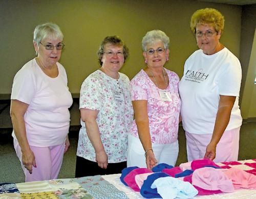 Extension Homemakers (from left) Chloe Haynes, of DeKalb County; Stephanie Jerabek, of Huntington County; Carol Baker, of Wells County; and Rita McCabe, of Huntington County display some of the lap quilts and turbans that were made at the camp.