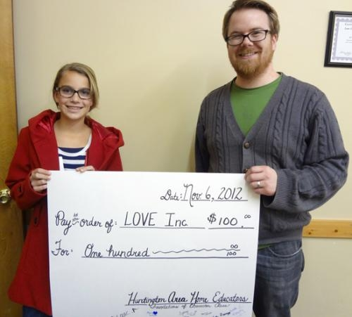 Huntington Area Home School student Sydney Kline (left) presents a check for $100 to Joey Spiegel, executive director of Love INC, after Kline successfully campaigned to win support for the organization.