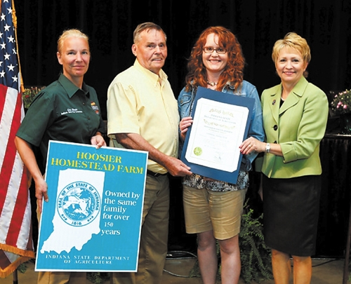 Wallace Riggers (second from left) and Audra Riggers (third from left) receive the Hoosier Homestead Farm award from Gina Sheets (left), director of the Indiana Department of Agriculture, and Lt. Gov Sue Ellspermann (right) on Aug. 7 at the state fair.