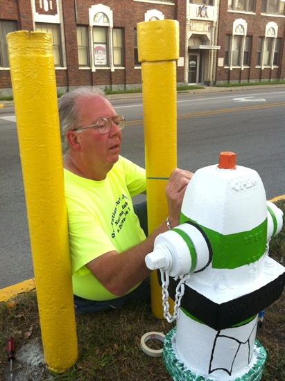 Barry Cochran, one of 24 artists participating in the Huntington Arts Initiative's fire hydrant art project, puts the finishing touches on his hydrant in preparation for the project's opening on Sept. 8.