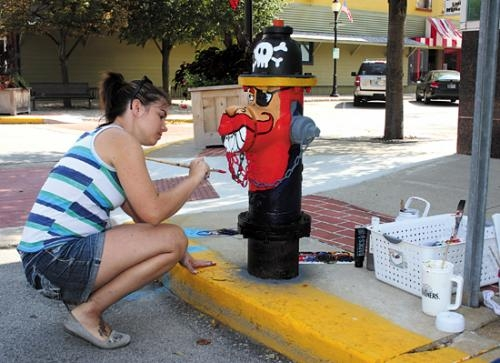 "Dana Spahr paints a fire hydrant outside the Courthouse Annex, in Huntington, on Thursday, Sept. 6. Spahr selected the letter ""P"" and decided to paint a pirate."