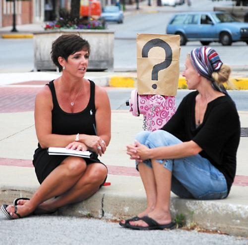 "Tami Capozza (left) and Angela Ellsworth sit in front of a hydrant from last year's Arts Initiative exhibit and discuss their ideas for this year's theme ""Down(town) By The Sea,"" which gives artists the opportunity to paint a downtown hydrant."