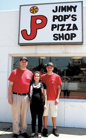 New owner James Coon (left) stands in front of Jimmy Pop's Pizza Shop, formerly known as Tasty Pizza.  Pictured also are Coon's wife Elizabeth Coon (center) and son Izaak Coon (right), who will also work at the business.