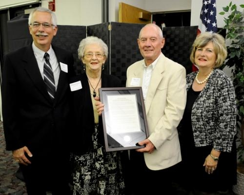 Ralph Johnson (third from left) and his wife Barbara Johnson (second from left) receive the Huntington University Foundation's Distinguished Service Award from Ed Vessels (left), foundation president, and Huntington University President Sherilyn Emberton.