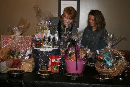 Heather Bowman (left) and Barb Young prepare some of the gift baskets that will be raffled off during the Wine and Beer Tasting March 8 at the Huntington Knights of Columbus hall.