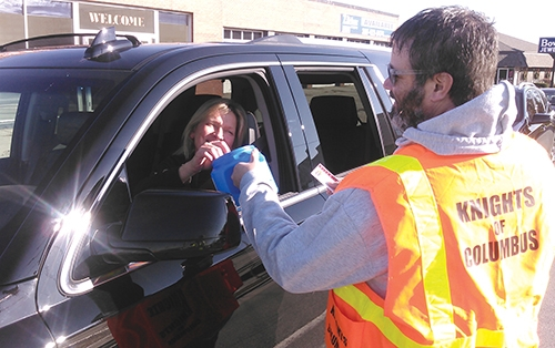 Knights of Columbus Council 1014 member Kevin Shipbaugh accepts a donation from a motorist during the KOC's annual Pitch-In road block last year. This year's event takes place Saturday, Dec. 1.