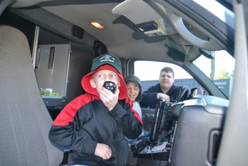 Parkview EMT Logan Ison (right) watches as Hunter Barron (left) tries out the radio while Eli Barron sits in the driver's seat of a Parkview EMS ambulance on Tuesday, Oct. 17. The boys' father was a volunteer firefighter and rescue squad member in Tennessee until losing his life in a car crash in July. The boys and their mother have since moved to Huntington and Sheriff Terry Stoffel arranged for the brothers to have their photo taken with the ambulance, a Hummer and a fire truck in honor of their late father.