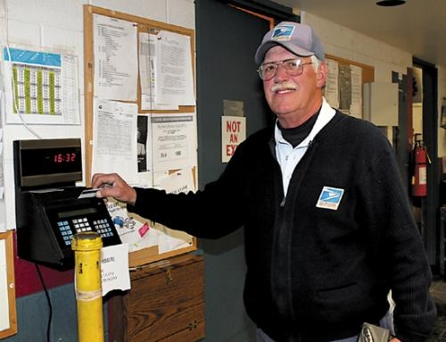 Larry D'Amato, a mail carrier with the Huntington Post Office, clocks out for the last time on Friday, Nov. 30, at the post office, in Huntington. D'Amato retires after spending 40 years with the post office.