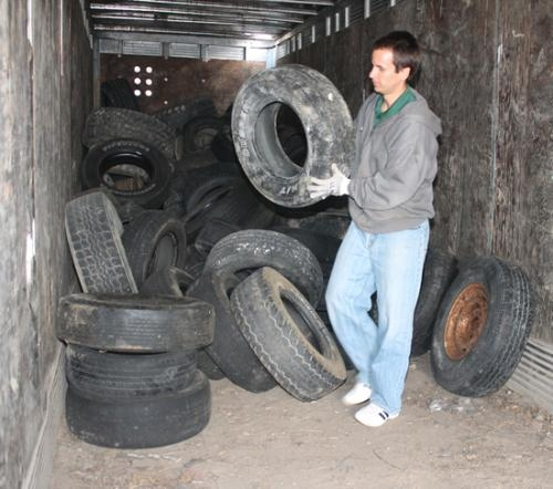 Jonathan Leist, Huntington County Solid Waste Management director, stacks tires in a trailer at the Huntington Landfill on Tuesday, Sept. 25. The landfill will accept up to six passenger car and truck tires and two Freon items per residence in Huntington