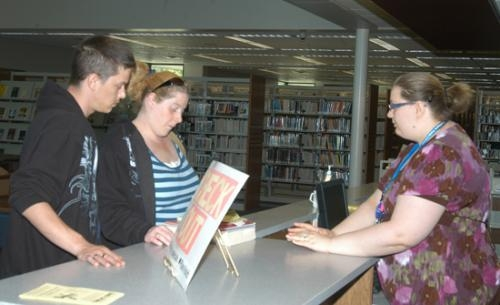 Jessi Brown (right) checks out books for Clint and Leanne Stockert on Thursday, May 6, at the Huntington City-Township Public Library's new circulation desk. The library's new north entrance will open today, Monday, May 10.