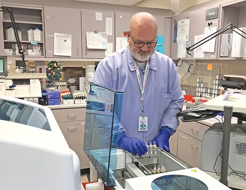 Greg Reed, clinical lab scientist at Parkview Huntington Hospital, loads samples into the new, faster analyzer in the PHH lab.