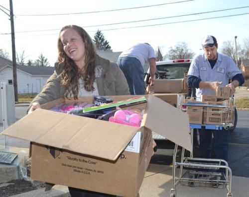 Sharon Aluma (left) and Dave Getman carry in boxes of toys and personal care items that employees of the Unilever Breyers plant in Huntington donated to Love INC. The gifts will be given to area residents in need at Christmas time.