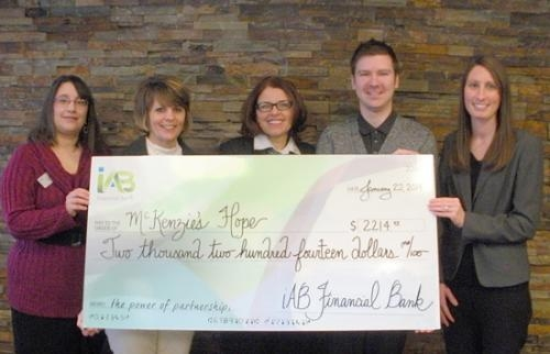 iAB financial bank employees (from left) Cathy Whitesel, Kim Heyde and Angie Kuhn hand off a donation check to (fourth from left) Wayne Stephan, McKenzie's Hope executive director and (right) Lindsi Walker, McKenzie's Hope board president.