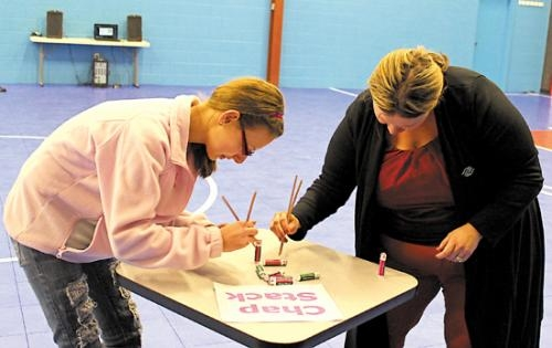 """Mandy Reber (right), executive director of the Boys & Girls Club of Huntington, and club member Autumn Elston play the """"Minute to Win it"""" game Chap Stack at the club's mentoring party on Feb. 1."""