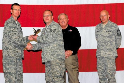 Staff Sgt. Phillip Thompson (second from left), 325th Maintenance Squadron precision guided munitions crew chief, accepts the Lt. Gen Leo Marquez Award from Col. Curtis Hafer, 325th Maintenance Group commander.